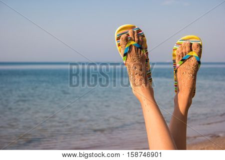 Woman's legs on sea background. Feet in flip flops. No problems and bustle. Vacation of dreams.