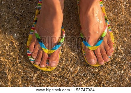 Woman's feet wearing flip flops. Transparent water and sand. At the ocean shore. Trip to a tropical island.