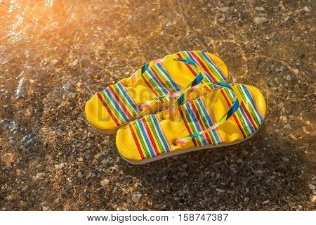 Flip flops on a shore. Sunlight and transparent water. Be closer to the sea. Spend vacation at exotic island.
