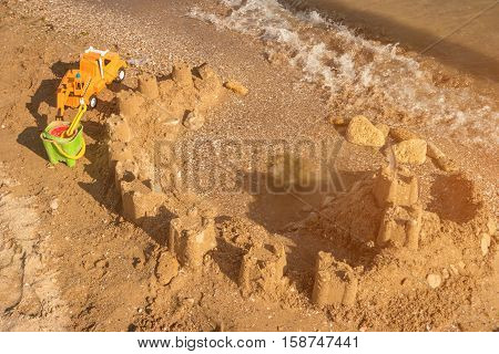 Sandcastle on the beach. Toy truck and sand. Build the strongest fortress. True pearl of architecture.