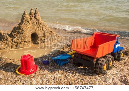Sandcastle on the shore. Toy truck on sand. Turn on your imagination. Dig and build.