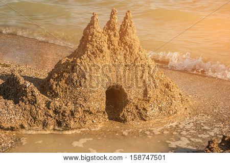 Sandcastle on shore. Small wave and sand. Fragility of art. The mighty kingdom.