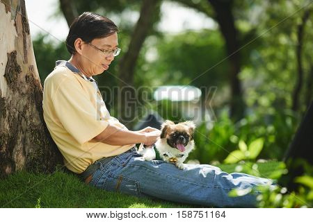 Asian senior man and his Pekingese dog resting in the park