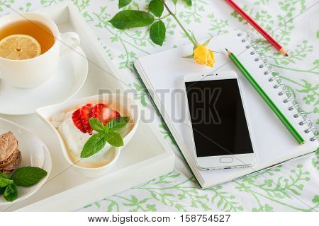 Wake up with breakfast in bed near notebook, mobile, pencils, yellow rose. Wake up nice and begin to plan a successful day concept. Horizontal. Close up.