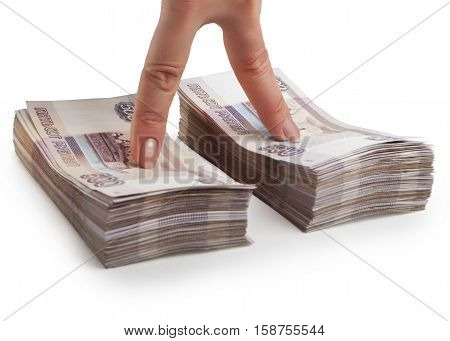 Two fingers of a hand at the stacks of paper Russian money