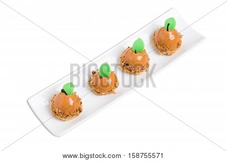 Delicious chocolate mirror glazed cakes with mastic mint leaves in form of pears. Isolated on a white background.