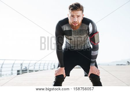 Tired runner near the sea. looking at camera. front view