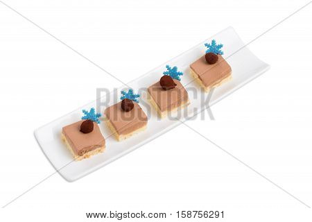 Delicious mousse cakes with chocolate truffles and blue mastic snowflakes. Isolated on a white background.
