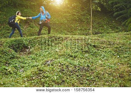 Traveler helping young woman to clime up the hill
