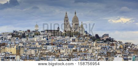 Montmartre and Sacre-Coeur church, Paris citiscape view over the roofs with dramatic autumn sky. France