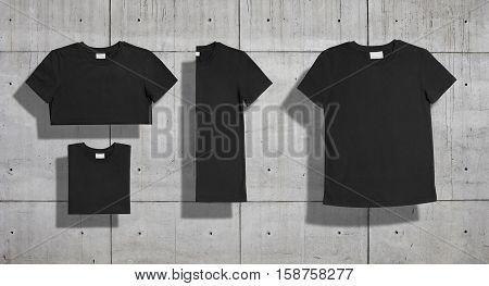 Black plain cotton shortsleeve crewneck t-shirt shot unfolded and folded in three different ways as a set isolated on concrete backround for merchandise