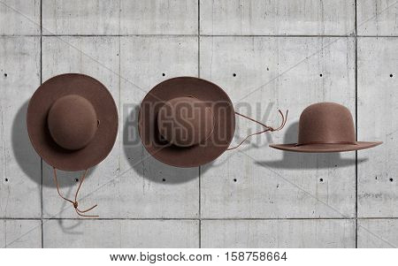 Coffee brown round felt cowboy hat with brown leather string shot from the top and from the side neutral gray concrete industrial background
