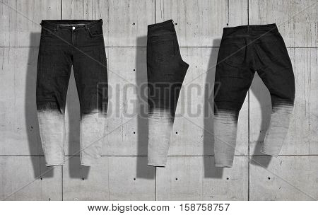 Pair of straight women's jeans with black to white gradient color shot from the front and the back and folded in half isolated on neutral industrial concrete background