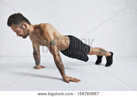 Strong brutal tattoed and ripped male athlete shows how to do pseudo push-ups, isolated on white spacious room, top position