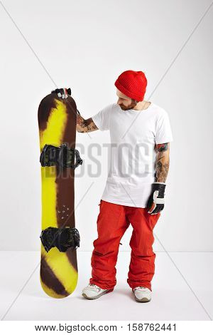 A young snowboarder wearing red pants, white unlabeled t-shirt and red beanie looking at his snowboard in studio with white walls