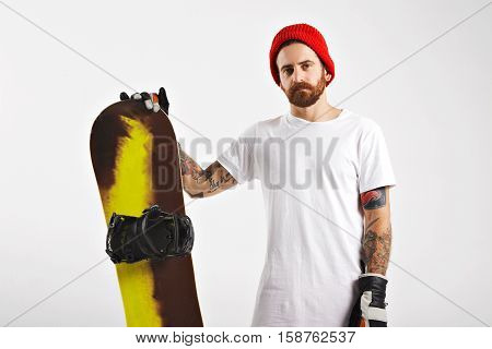 Tattooed and bearded young man in plain white cotton t-shirt, red beanie and leather snowboard glasses holding a snowboard isolated on white