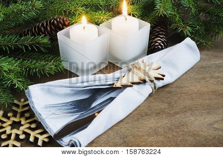 Rustic Christmas Table Setting for Christmas Eve. Winter Holydays. Cutlery on linen napkin candles and fir branches on rustic wooden background - country style. Selective focus space for text.