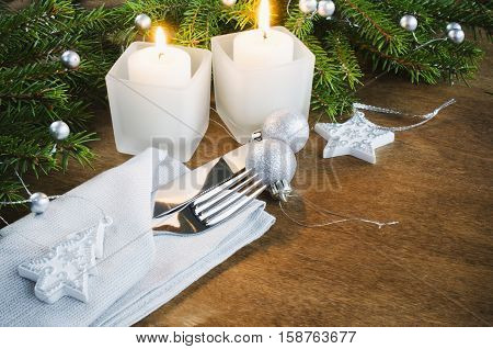 Table Place Setting for Christmas Eve. Winter Holydays. Christmas background. Cutlery on napkin candles and fir branches on rustic wooden background. Selective focus space for text.