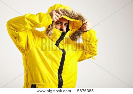 Close up shot of a young man putting up coat of his yellow snowboarded parka in a studio with white walls