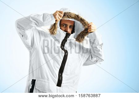 Attractive male model in a studio with white walls putting on the good of his bright white snowboarding anorak