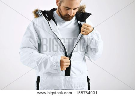 Serious attractive young man zipping up his snowboarding white jacket over unlabeled white t-shirt isolated on white