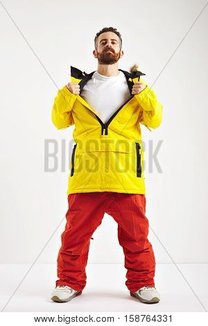 Snowboarder in red pants and yellow anorak opening up the front of his jacket to show plain white cotton t-shirt isolated on white