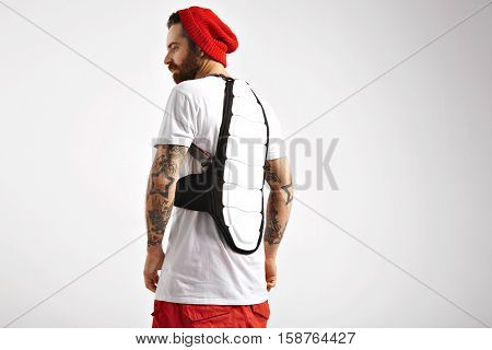 Attractive male model demonstrating snowboarding back protector in studio with white walls