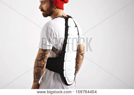 Back of a serious muscular young man with tattoos wearing snowboarding back protector isolated on white