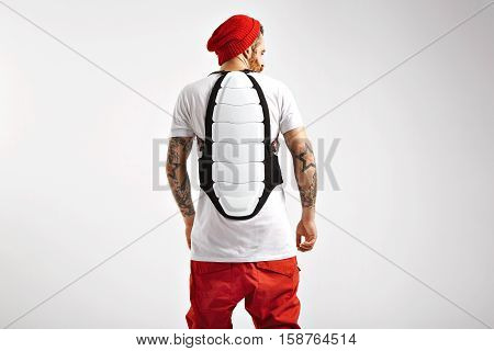 Back shot of a muscular young snowboarder wearing white and black back protector over his plain white cotton t-shirt isolated on white