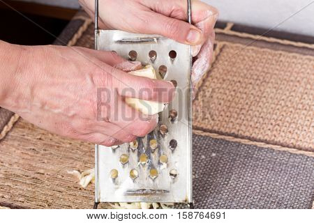 Male hands grating butter for dough on a kitchen table as a background.