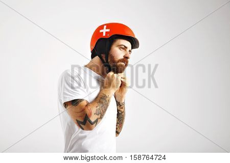 Muscular tattooed young man in white t-shirt closing the strap of his bright red safeguard snowboarding helmet isolated on white