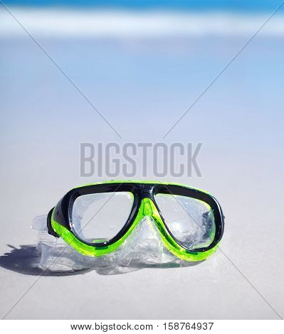 green snorkel and waterproof mask lying on sand behind blue sky and ocean