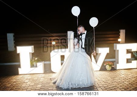 Stylish Wedding Couple With Lights Balloons Stay And Kisses Near Great Big Letter Word Love With Lig