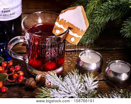 Top view mug of hot alcohol beverage and tasty cookie in house form decoration drink. Winter hot drink. Hot mulled wine with cookie.