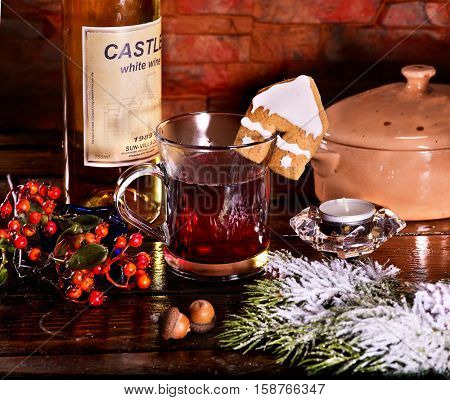 Christmas cookies in form of house is decorated with Christmas glass mug with hot winter drink. Warming mulled wine with berry. Top view.