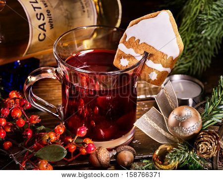Close up of glass mug of mulled punch decorated ginger snap and Christmas ball. Gingerbread cookie in form of house on mug.