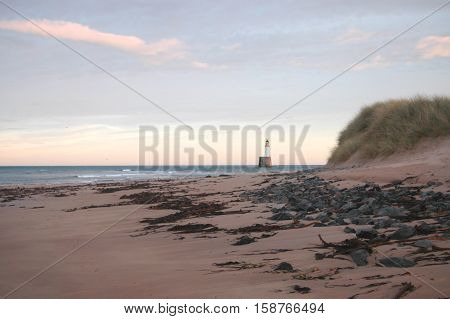 The iconic Rattray Head lighthouse, one of the famous `Stevenson` lighthouses, on the North East Coast of Scotland between Peterhead and Fraserburgh.