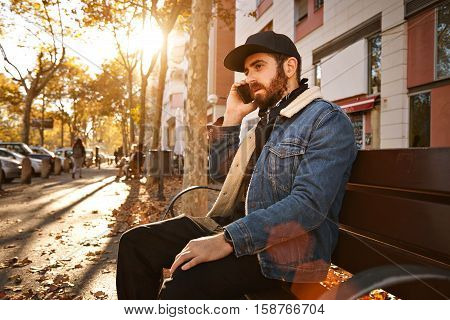 Quiet sunlit picture of a fall in the city with a hip young man sitting on a bench talking on his smartphone
