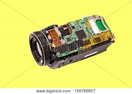 Disassembled compact camcorder. Close-up. Isolated on a yellow background.