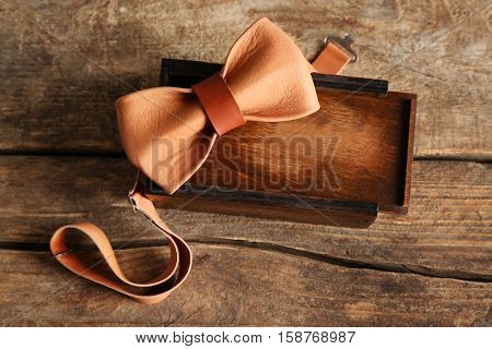 Leather bow tie and gift box on wooden background