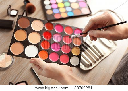 Female hands with palette of lipsticks and tonal foundation, closeup