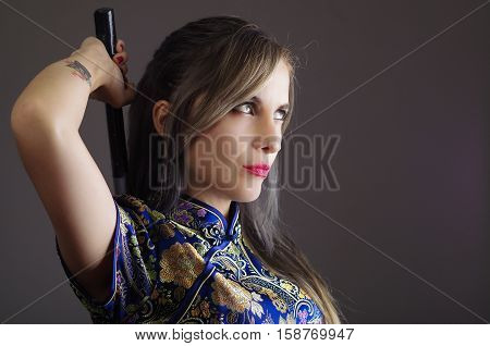 Samurai woman dressed in traditional colorful flower pattern asian silk dress, holding arm over shoulder grabbing sword hidden behind back, facing camera, ninja concept.