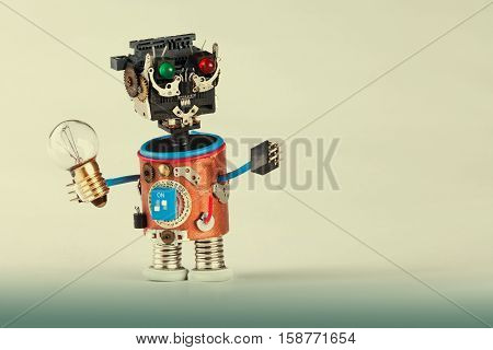 Mechanical robot with light bulb. Plastic head colored green red eyes electric wire hands gears cog wheel and clock parts mechanism. Fun toy character concept. Gradient background copy space