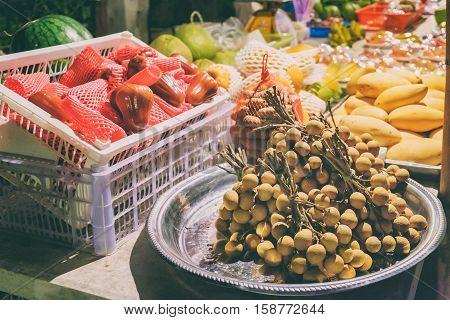 Fresh fruit market in Asia at night. Longan bundles, mango, watermelon, rose apple. Exotic street food