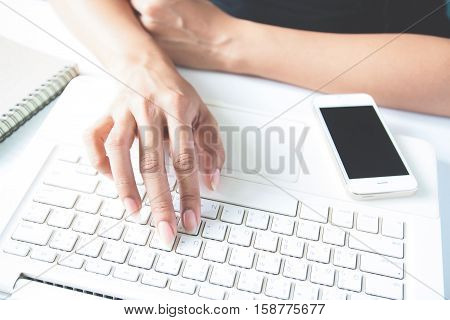Hands holding smartphone credit card and using laptop. Online shopping