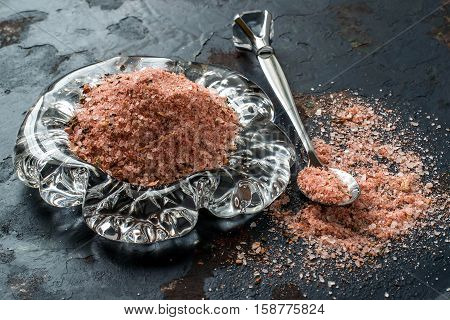 Special pink Adygei salt with spices (Russia) in glass plate and spoon on a dark textured background. Prepared according to the old recipe with garlic and spices. Useful economically spent