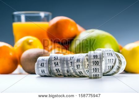 Measure tape and fresh fruit in the background. Healthy lifestyle diet with fresh tropical fruits.