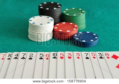 Stacks of poker chips with a deck of cards sprayed out face up