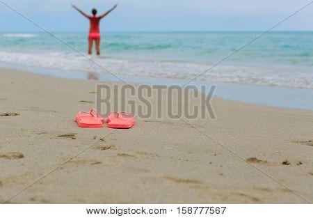 flip flops and happy woman swim at tropical beach