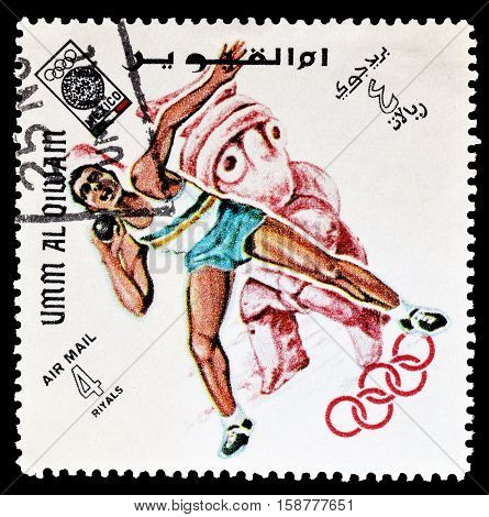 UMM AL QIWAIN - CIRCA 1968 : Cancelled postage stamp printed by Umm Al Qiwain, that shows Shot putting.